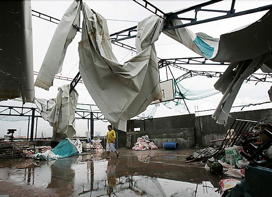 A worker walks past damage brought by strong winds from typhoon Conson at a roof-deck basketball court in suburban Manila on Wednesday, July 14, 2010. The Philippines' first typhoon of the year prompted flight and ferry cancellations, school closures, and warnings of floods and landslides. (AP Photo/Aaron Favila)