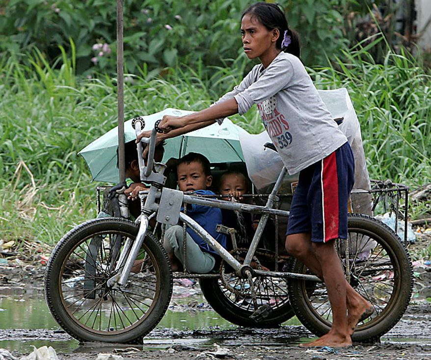A barefoot mother pushes a tricycle with her children on board as they look for a dry place to spend the night after their shanty collapsed in the onslaught of typhoon Conson on Wednesday, July 14, 2010, at Taytay township, Rizal province, east of Manila. The Philippines' first typhoon of the year prompted flight and ferry cancellations, school closures, and warnings of floods and landslides. (AP Photo/Bullit Marquez)