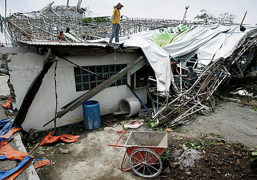 Filipinos try to arrange a tarpaulin from a billboard that collapsed on top of a house because of strong winds from typhoon Conson in Muntinlupa, Philippines, south of Manila, on Wednesday, July 14, 2010. The first typhoon to lash the Philippines this year killed at least 26 people and left at least 38 others missing. No one was injured during this incident. (AP Photo/Aaron Favila)