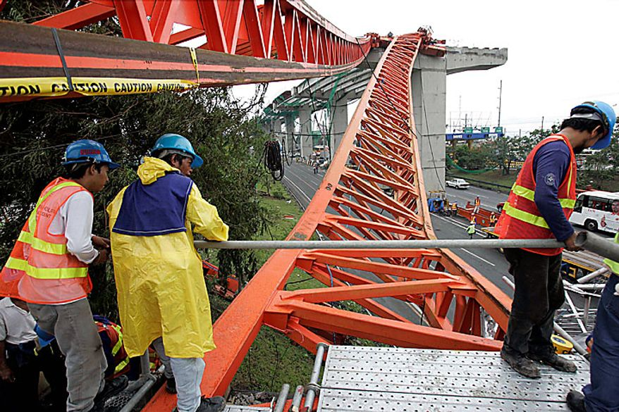 Workers place a makeshift bridge on one of the beams of a collapsed crane brought down by strong winds from typhoon Conson on the South Luzon Expressway in suburban Manila on Wednesday, July 14, 2010. The Philippines' first typhoon of the year prompted flight and ferry cancellations, school closures, and warnings of floods and landslides. (AP Photo/Aaron Favila)