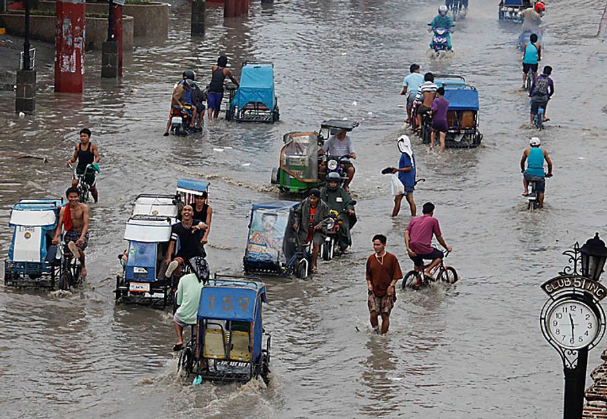 Residents wade through a flooded street in Las Pinas, Philippines, south of Manila, on Wednesday, July 14, 2010, hours after typhoon Conson lashed Manila and nearby areas. (AP Photo/Bullit Marquez)