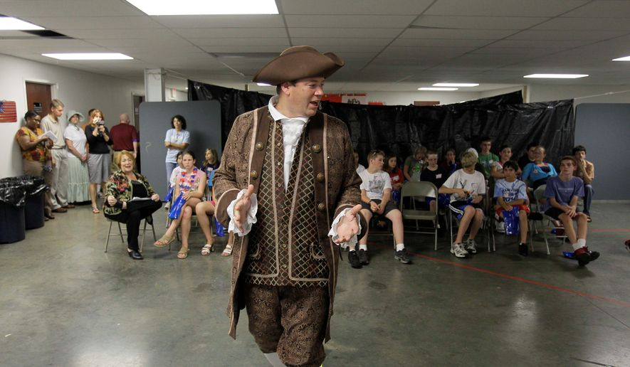 "ASSOCIATED PRESS PHOTOGRAPHS Tim Fairfield wears period clothing as he talks to children about the merits of free enterprise on the first night of a Vacation Liberty School in Georgetown, Ky., on Monday. ""If we're going to take our country back, we've got to remember where we came from - not only as adults, but we need to teach our children,"" said Mr. Fairfield, one of the teachers."