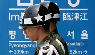 ASSOCIATED PRESS South Korean soldiers pass a signboard near the demilitarized zone of Panmunjom, showing distances to Pyongyang and Seoul.