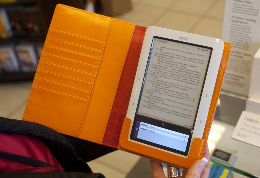 ** FILE ** In this Feb. 9, 2010 file photo, a customer reads a Nook electronic reader at a Barnes & Noble book store in Hackensack, N.J. (AP Photo/Mark Lennihan, file)