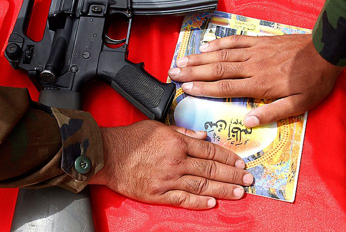 Recruited Afghan soldiers place their hands on a copy of the Quran, Islam's holy book, during an oath taking ceremony at the Ghazi Military Training Center, where they are being trained by Turkish military officers of the NATO-led International Security Assistance Force (ISAF) in Kabul, Afghanistan, on Thursday, July 15, 2010. (AP Photo/Musadeq Sadeq)