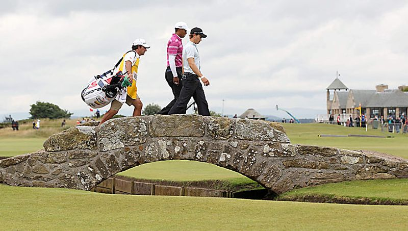 Tiger Woods of the United States, center, and Colombia's Camilo Villegas, right, and caddie Brett Waldman walk across the Swilken Burn bridge on the 18th hole during the first round of the British Open Golf Championship on the Old Course at St. Andrews, Scotland, Thursday, July 15, 2010. (AP Photo/Alastair Grant)
