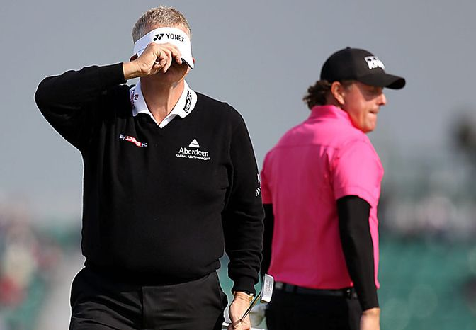 Scotland's Colin Montgomerie, left, and Phil Mickelson of the United States stand on the 10th hole during the first round of the British Open Golf Championship on the Old Course at St. Andrews, Scotland, Thursday, July 15, 2010. (AP Photo/Alastair Grant)