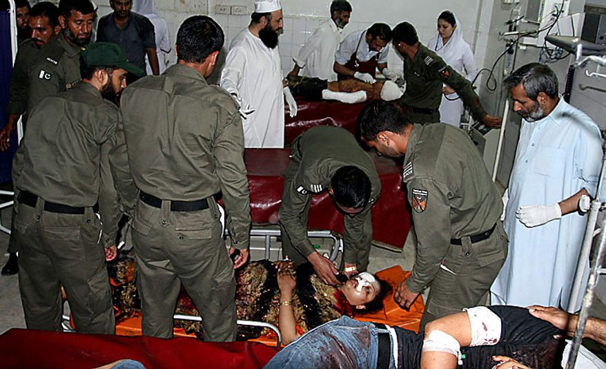 Pakistani rescue workers and hospital staff attend people injured in a suicide attack at a local hospital in Peshawar, Pakistan on Thursday, July 15, 2010. An apparent suicide bombing near a bus terminal in Pakistan's Swat Valley killed five people and wounded at least 58 on Thursday, officials said, a sign that Islamist militants remain active in the northwest region despite a massive army operation.(AP Photo/Mohammad Sajjad)