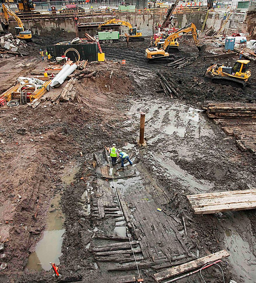 Archeologists, center, take measurements of the wood hull of a 32-foot-long (9.75 meters) 18th century boat at the World Trade Center site, Thursday, July 15, 2010 in New York. (AP Photo/Mark Lennihan)