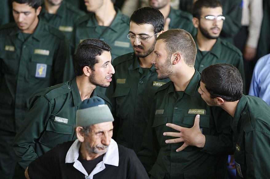 Members of Iran's elite Revolutionary Guard talk as they prepare for Friday prayers, at the Tehran University campus in Tehran, Friday, July 16, 2010. A Sunni insurgent group said it carried out a double suicide bombing against a Shi'ite mosque in southeast Iran to avenge the execution of its leader, as Iranian authorities Friday said the death toll rose to 27 people, including members of the elite Revolutionary Guard. (AP Photo/Vahid Salemi)