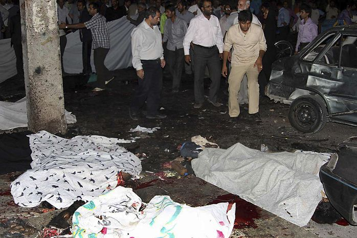 In this picture released by  Iran's official Islamic Republic News Agency, bodies of victims of bomb blasts lie on the street, in the city of Zahedan, 940 miles southeast of the capital Tehran Thursday, July 15, 2010. Twin bombings killed more than 20 people outside a mosque in southeastern Iran on Thursday _ including members of the powerful Revolutionary Guard _ in attacks that came less than a month after Iran hanged the leader of a militant insurgent group in the region. (AP Photo/Islamic Republic News Agency, IRNA)