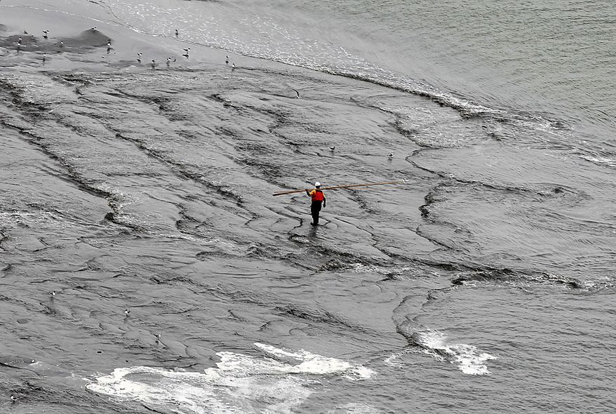 A worker walks through the water as a berm system is constructed on the northern end of the Chandeleur Islands, La., Thursday, July 15, 2010. A tightly fitted cap was successfully keeping oil from gushing into the Gulf of Mexico for the first time in three months, BP said Thursday. (AP Photo/Dave Martin)
