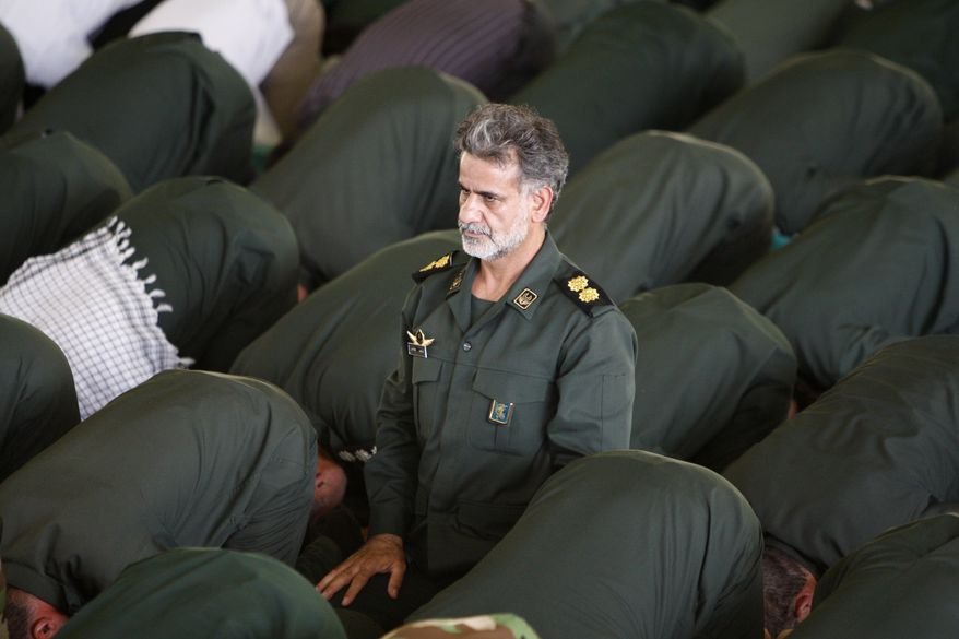 A lieutenant colonel of the Iranian elite Revolutionary Guard, attends Friday prayers with his colleague at Tehran University campus in Tehran, Iran, Friday, July 16, 2010. A Sunni insurgent group said it carried out a double suicide bombing against a Shiite mosque in southeast Iran to avenge the execution of its leader, as Iranian authorities Friday said the death toll included members of the elite Revolutionary Guard. (AP Photo/Vahid Salemi)