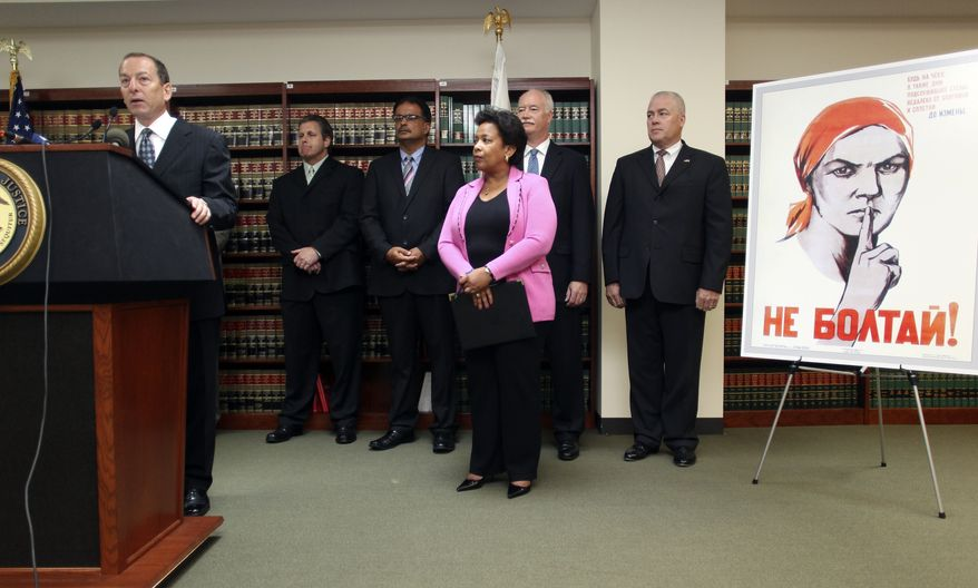 """Assistant Attorney General Lanny Breuer, left, speaks to the media as Loretta Lynch, center, U.S. Attorney for the Eastern District of New York, and other law enforcement officials announce charges against doctors, health care company owners, executives and others in a case of alleged false medicare billing at a news conference in the U.S. Attorney's office in the Brooklyn borough of New York, Friday, July 16, 2010. The poster at right, which says in Russian """"Do Not Gossip,"""" was, allegedly, in the back room of a doctor's office where patients were being bribed for their cooperation in the scheme. (AP Photo/Robert Mecea)"""