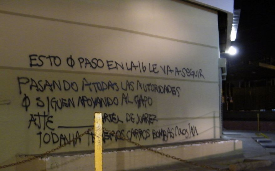 "**FILE** A wall at a shopping center is covered by graffiti that reads in Spanish: ""What happened on the 16 (street) is going to keep happening to all the authorities that continue to support the Chapo (Guzman), sincerely, the Juarez Cartel. We still have car bombs (expletive) ha ha."" Cartel assailants laid a trap for federal police and attacked them with a car bomb on July 15, the first time a drug cartel have used explosives to attack Mexican security forces, marking an escalation in the country's drug war. (Associated Press)"