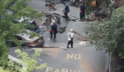 A police officer walks with a search dog as other rescue officials walk on the rubble after the front of an apartment building and a parking garage collapsed Friday, July 16, 2010, in Hackensack, N.J. (AP Photo/ Mel Evans)