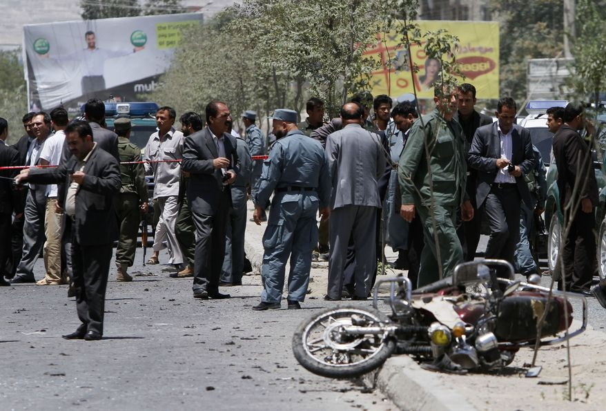 Afghan police and other officials inspect the scene of a suicide bombing in Kabul, Afghanistan, that killed three civilians on Sunday, July 18, 2010, two days before an international conference of representatives from about 60 nations, an Afghan official said. The bomber was on foot, and his target was unclear, according to police official Abdul Ghafor Sayedzada. (AP Photo/Rahmat Gul)