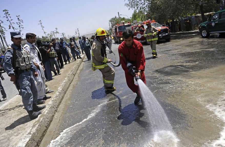 Afghan firefighters hose down the scene of a suicide bombing in Kabul, Afghanistan, on Sunday, July 18, 2010, two days before an international conference that bring together representatives from about 60 nations. (AP Photo/Hossein Fatemi)
