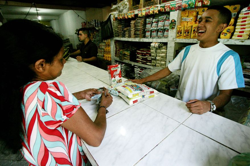 A customer buys groceries at Mercal, a government-owned market in Caracas. The markets are part of Mr. Chavez's effort to counter 31 percent inflation in a recession economy.