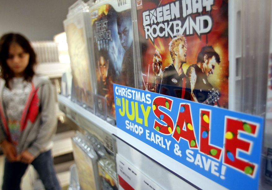 """Video games are among items promoted in a """"Christmas in July"""" sale at a Toys 'R' Us store in New York on Monday, July 19, 2010. (AP Photo/Bebeto Matthews)"""