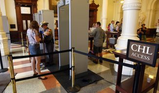 """** FILE ** A sign for those with concealed handgun licensees (CHL) is seen as people pass through one of four new metal detectors at the Texas Capitol in Austin on June 3, 2010. A shooting incident in January outside the Capitol prompted lawmakers to order metal detectors at public entrances and the creation of a separate lane for CHL holders to get through them. Capitol insiders are now signing up in droves for the course that will get them a license, now known as the """"express pass."""" (AP Photo/American Statesman, Ricardo B. Brazziell)"""
