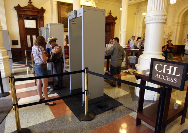 "** FILE ** A sign for those with concealed handgun licensees (CHL) is seen as people pass through one of four new metal detectors at the Texas Capitol in Austin on June 3, 2010. A shooting incident in January outside the Capitol prompted lawmakers to order metal detectors at public entrances and the creation of a separate lane for CHL holders to get through them. Capitol insiders are now signing up in droves for the course that will get them a license, now known as the ""express pass."" (AP Photo/American Statesman, Ricardo B. Brazziell)"