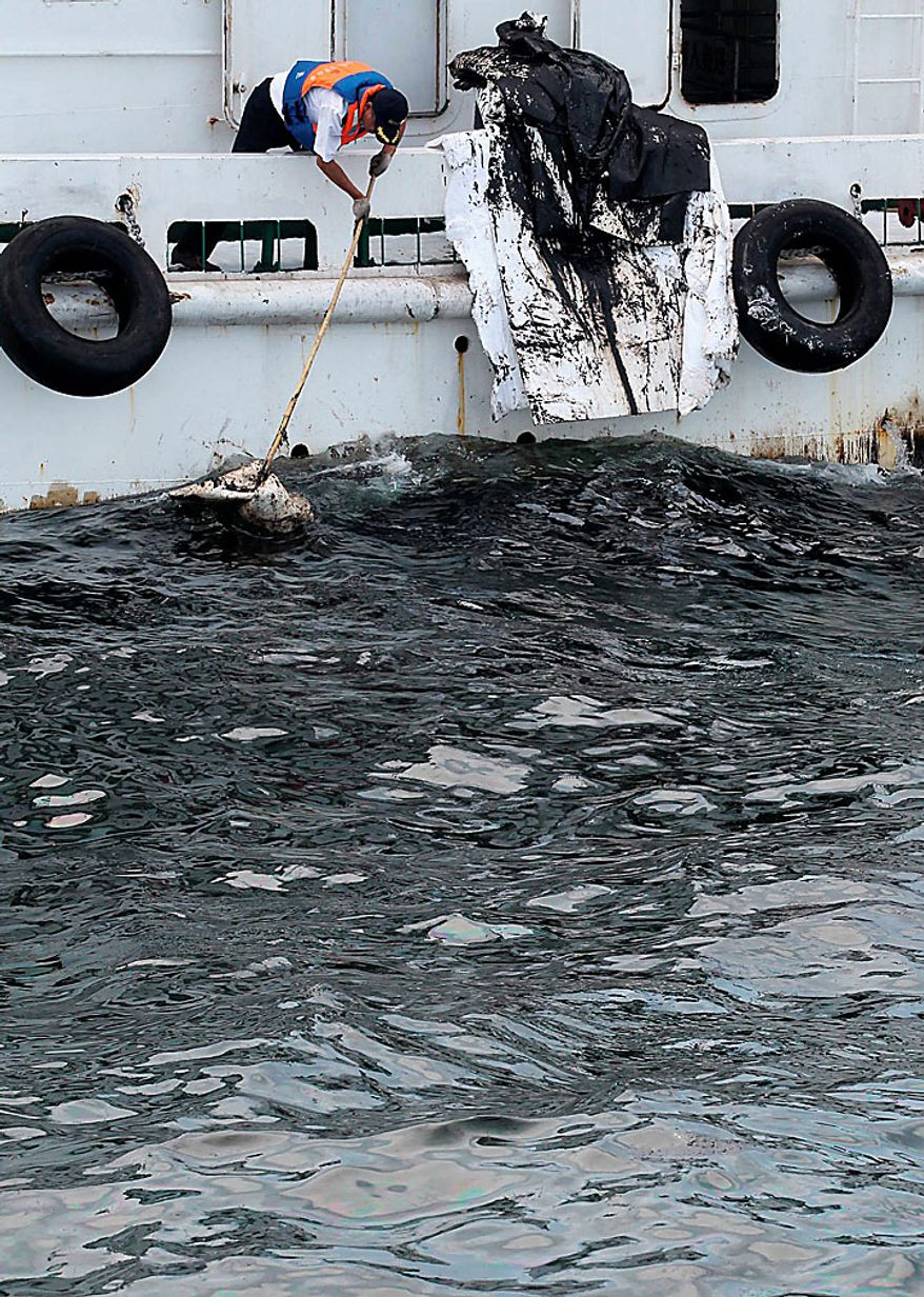 In this photo taken Sunday, July 18, 2010, a Chinese worker tries to soak up oil from a spill in the sea near Dalian in northeast China's Liaoning province. Efforts were under way to contain and clean up a large oil slick after pipeline explosions at a northeastern Chinese port sent greasy black plumes into the ocean, state media reported Sunday. (AP Photo)