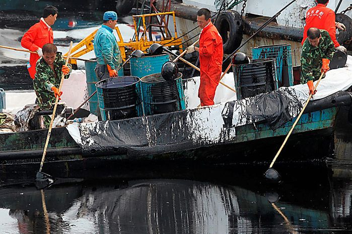 In this photo taken Sunday, July 18, 2010, Chinese workers scoop up oil from a spill in the sea near Dalian in northeast China's Liaoning province.    Efforts were under way to contain and clean up a large oil slick after pipeline explosions at a northeastern Chinese port sent greasy black plumes into the ocean, state media reported Sunday. (AP Photo)