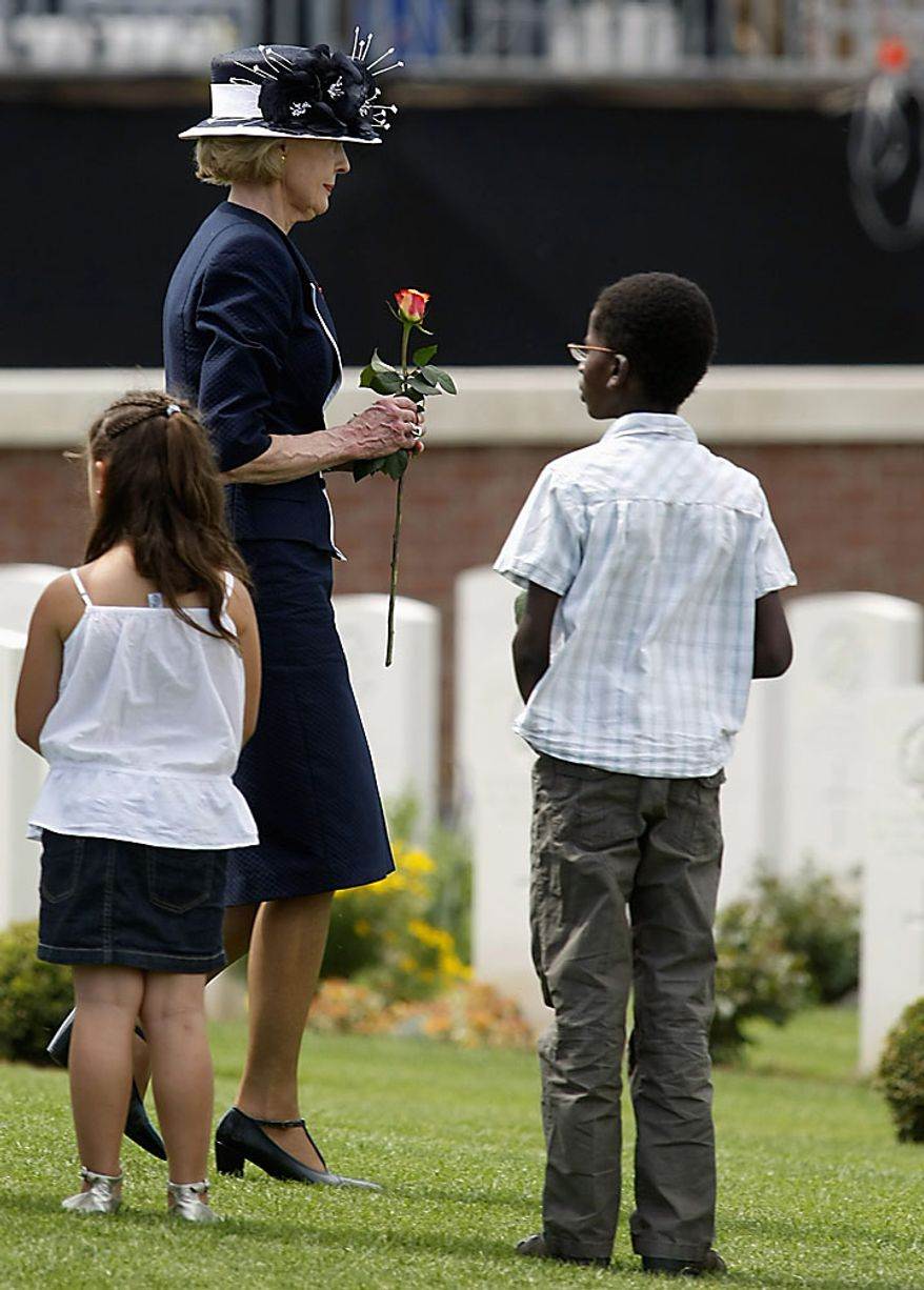 Australia Governor General Quentin Bryce prepares to put a rose on the coffin of an Australian unknown soldier during a ceremony at the British Australian cemetary of Fromelles, Northern France, Monday, July 19, 2010. Royalty, governments and relatives on Monday honored Australian and British soldiers whose remains were discovered in mass graves on the 94th anniversary of the World War I battle of Fromelles in northern France.(AP Photo/Remy de la Mauviniere)