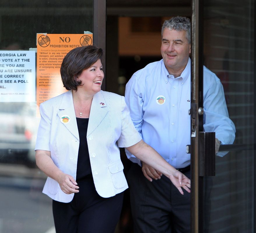 Republican gubernatorial candidate Karen Handel and her husband, Steve, leave a polling spot in Roswell, Ga. Sarah Palin has endorsed Mrs. Handel, who has recently surged to the top of polls. (Associated Press)