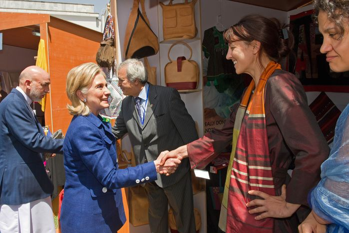Afghan President Hamid Karzai (left) and U.S. Secretary of State Hillary Rodham Clinton (second from left) greet merchants as they tour a crafts bazaar in Kabul, Afghanistan, on Tuesday, July 20, 2010. Mrs. Clinton is in Kabul to attend an international conference on the future of Afghanistan. (AP Photo/Paul J. RICHARDS, Pool)