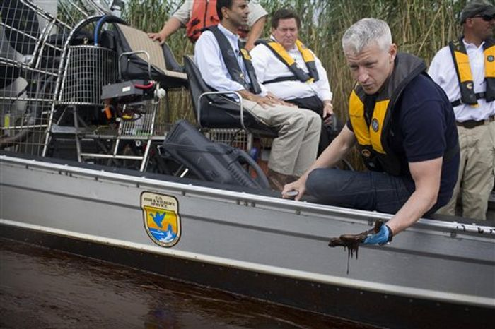 FILE - In this May 26, 2010 publicity image released by CNN, CNN's Anderson Cooper, right, inspects the oil spill during a tour with Louisiana Gov. Bobby Jindal, background left, of the contaminated areas in Blind Bay, La. (AP Photo/CNN, Shaul Schwarz)