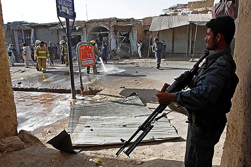An Afghan policeman stands guard at the site of a suicide bomibng in Kandahar city, south of Kabul, Afghanistan, Tuesday, July 20, 2010. A suicide bomber struck hiding explosives in a cart topped with bottles of juice for sale, Afghan officials. Two civilians were injured in the blast. (AP Photo/Allauddin Khan)