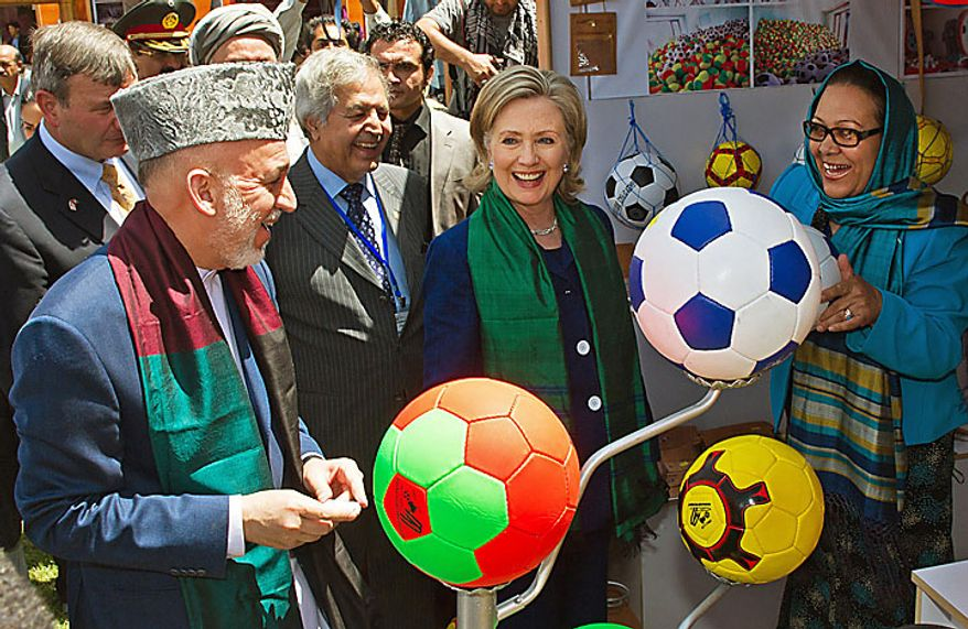 Afghan President Hamid Karzai, left, and U.S. Secretary of State Hillary Rodham Clinton, center right, tour a crafts bazaar in Kabul on Tuesday July 20, 2010, as they attend an international conference on Afghanistan. (AP Photo/Paul J. RICHARDS, Pool)