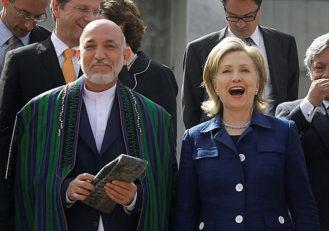 U.S. Secretary of State Hillary Rodham Clinton, right, laughs as Afghan President Hamid Karzai and rest of the foreign ministers prepare to pose for a group photo after the Kabul International Conference at the Foreign Ministry in Kabul, Afghanistan on Tuesday, July 20, 2010. (AP Photo/Musadeq Sadeq)