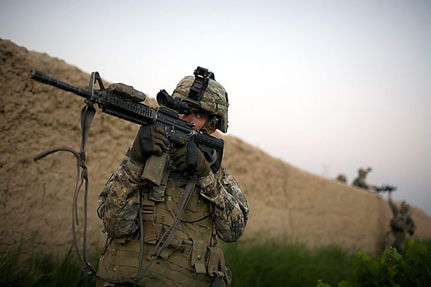 A U.S. Army soldier from the 1-320th Alpha Battery, 2nd Brigade of the 101st Airborne Division points his rifle during a patrol towards COB Nolan, in the volatile Arghandab Valley, Kandahar, Afghanistan, Tuesday, July 20, 2010. (AP Photo/Rodrigo Abd)