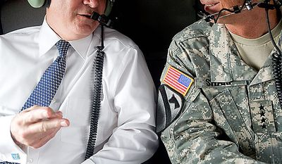 """A photo provided by the Defense Department shows Defense Secretary Robert M. Gates, left, speaking to Army Gen. Walter L. """"Skip"""" Sharp, commander of U.S. Combined Forces Command and commander of U.S. Forces Korea, on board a helicopter to Camp Casey in South Korea to speak with U.S. and Korean troops, Tuesday July 20, 2010. (AP Photo/Cherie Cullen)"""