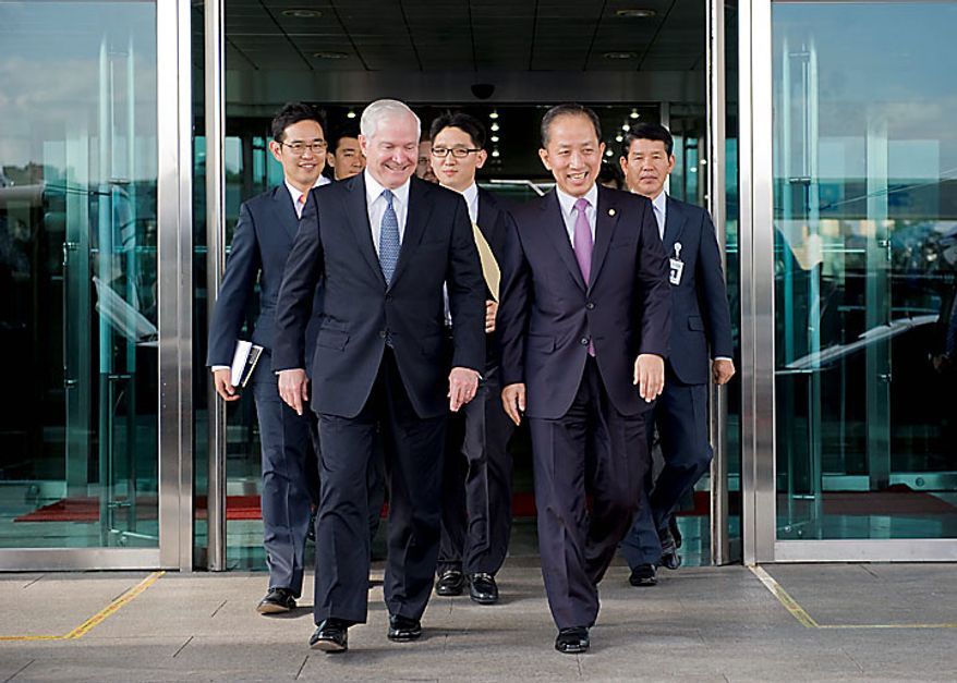 Defense Secretary Robert M. Gates, front left, and Korean Minister of National Defense Kim Tae Young, front right, leave the Ministry of Defense building in Seoul South Korea, Tuesday July 20, 2010. (AP Photo/Cherie Cullen)