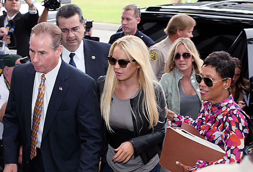 Lindsay Lohan, center, and her attorney Shawna Chapman Holley, arrive at the Beverly Hills courthouse Tuesday, July 20, 2010, in Beverly Hills, Calif.  (AP Photo/Nick Ut)
