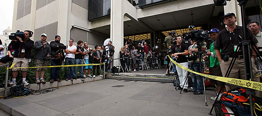 Dozens of media representatives and other observers await the arrival of Lindsay Lohan at the Beverly Hills courthouse Tuesday, July 20, 2010.  (AP Photo/Nick Ut)