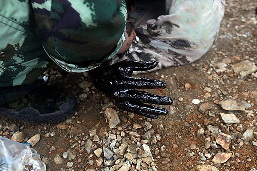 In this photo released by Greenpeace, oil covered the hand of a firefighter who was overwhelmed by the thick oil spill while attempting to fix an underwater pump is seen after he is pulled ashore by his colleagues in Dalian, China, on Tuesday, July 20, 2010. Crude oil started pouring into the Yellow Sea off a busy northeastern port after a pipeline exploded late last week, sparking a massive 15-hour fire. The government says the slick has spread across a 70-square-mile stretch of ocean. (AP Photo/Jiang He, Greenpeace)