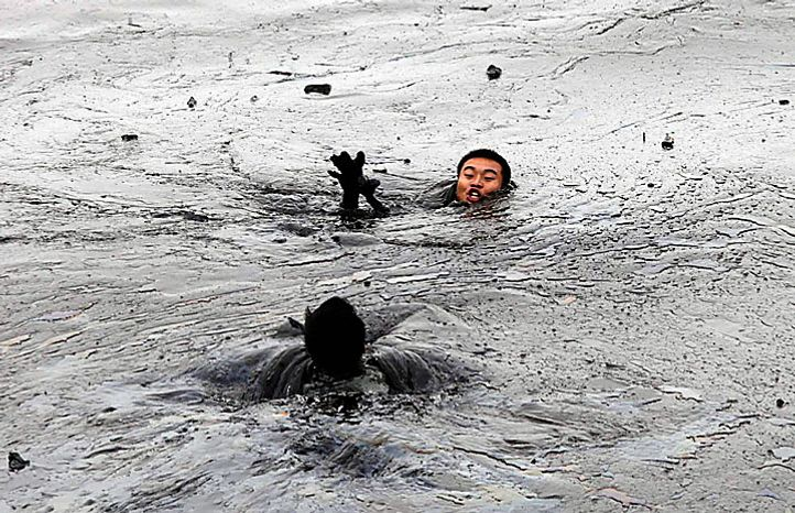 In this photo released by Greenpeace, a firefighter rushes to aid his colleague who ran into trouble amid thick oil cover as they attempted to fix an underwater pump in Dalian, China, on Tuesday, July 20, 2010. Crude oil started pouring into the Yellow Sea off a busy northeastern port after a pipeline exploded late last week, sparking a massive 15-hour fire. The government says the slick has spread across a 70-square-mile stretch of ocean. (AP Photo/Jiang He, Greenpeace)