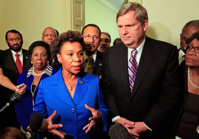 Associated Press photographs Agriculture Secretary Tom Vilsack stands with Rep. Barbara Lee, California Democrat, and other Congressional Black Caucus members after their meeting on Capitol Hill on Wednesday to discuss the Shirley Sherrod case.