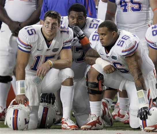 FILE - In this Dec. 5, 2009, file photo, Florida quarterback Tim Tebow (15), defensive end Carl Johnson (57) and offensive lineman Maurkice Pouncey (56) look on late in the fourth quarter of Florida's 32-13 loss to Alabama in the NCAA college football Southeastern Conference championship game in Atlanta. Florida and the NCAA are investigating an allegation that Pouncey, who was selected 18th overall in this year's NFL draft, received $100,000 from a representative of a sports agent before last season ended, ESPN.com reported Monday, July 19. (AP Photo/John Amis, File)