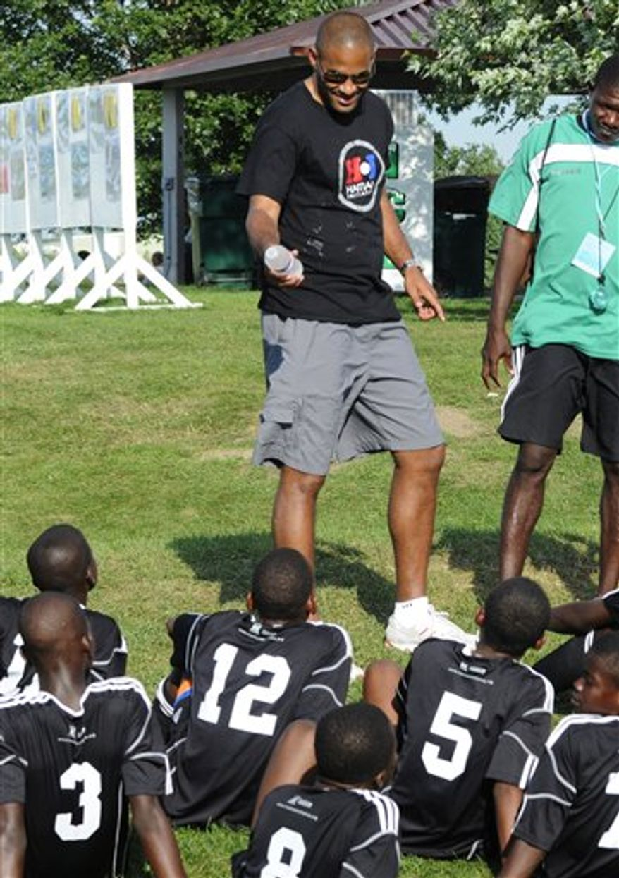In a photo made July 14, 2010, Haitian youth soccer players listen to former Major League Soccer player Tony Sanneh, left, during the USA Cup soccer tournament in Blaine, Minn. The team of 14 and 15-year-old players was brought to Minnesota with money raised by his foundation and the L.A. Galaxy soccer club to to play in the largest youth tournament in the country. (AP Photo/Jim Mone)