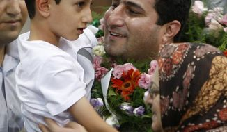 Shahram Amiri, an Iranian nuclear scientist who disappeared a year ago, holds his 7-year-old son Amir Hossein as he arrives at the Imam Khomeini airport just outside Tehran Thursday, July 15, 2010. Iranian news agencies reported Wednesday that Mr. Amiri provided valuable information on the CIA. (AP Photo/Vahid Salemi)