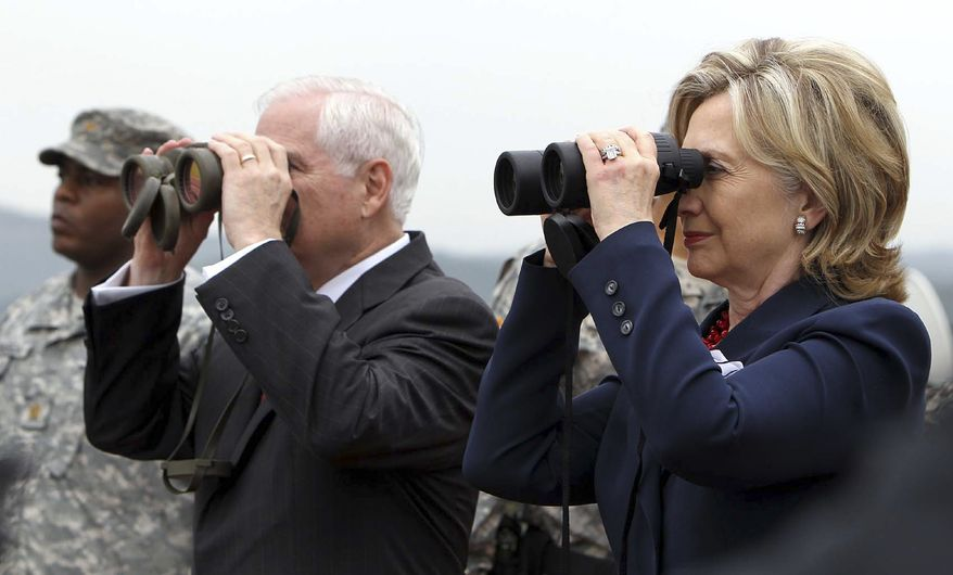 Secretary of State Hillary Rodham Clinton, right, and Defense Secretary Robert Gates look at North Korea using binoculars at a guard post in Camp Oulette neat the truce village of Panmunjom in the demilitarized zone that separates the two Koreas since the Korean War, north of Seoul, South Korea, Wednesday, July 21, 2010. (AP Photo/ Korea Pool) *