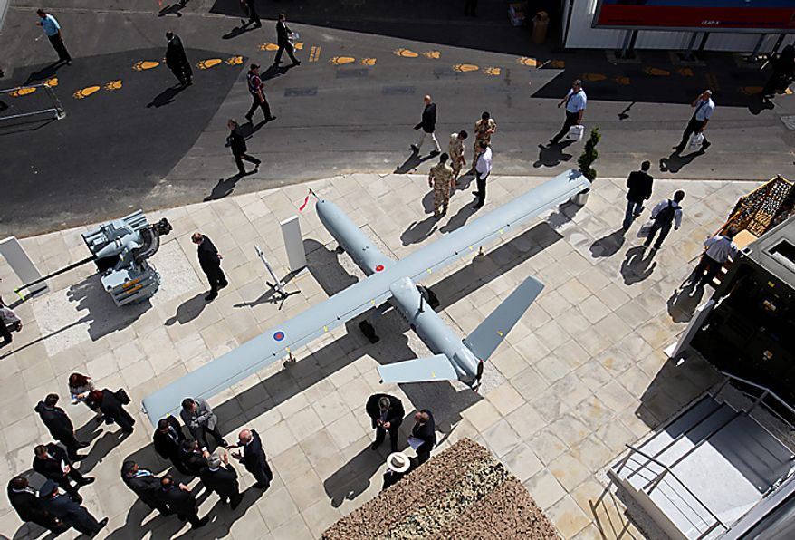 Visitors look at a Thales UK Watchkeeper drone on display on the third day of the Farnborough International Airshow in Farnborough, England, on Wednesday, July 21, 2010. The Farnborough International Airshow is being held from July 19-25. Photographer: Simon Dawson/Bloomberg