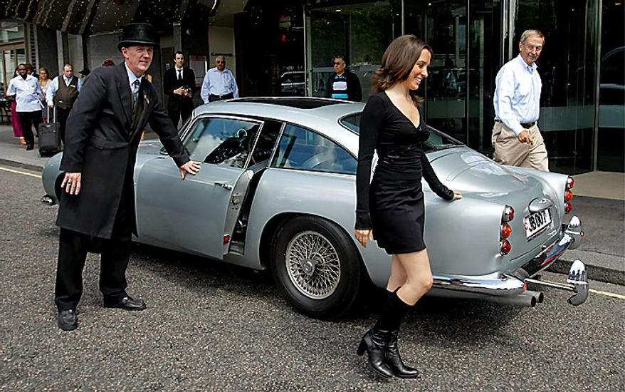 A woman walks away after modeling beside the original Aston Martin DB5 car driven by Sean Connery in the James Bond films Goldfinger and Thunderball as it displayed for the media in London, Wednesday, July 21, 2010. The car is estimated to fetch in the region of $4.6 million when it is sold at auction in London on Oct. 27.  (AP Photo/Matt Dunham)