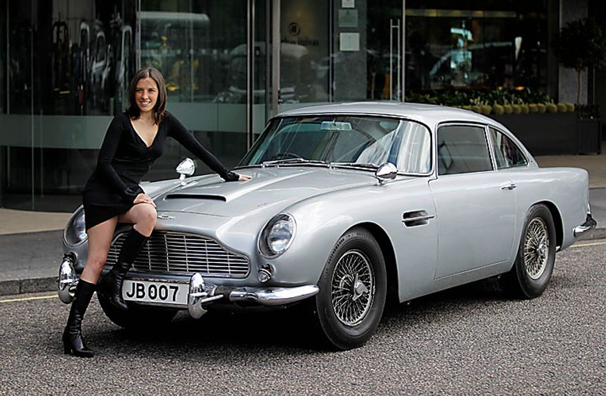 A woman poses on the original Aston Martin DB5 car driven by Sean Connery in the James Bond films Goldfinger and Thunderball as it displayed for the media in London, Wednesday, July 21, 2010.  The car is estimated to fetch in the region of $4.6 million when it is sold at auction in London on Oct. 27.  (AP Photo/Matt Dunham)